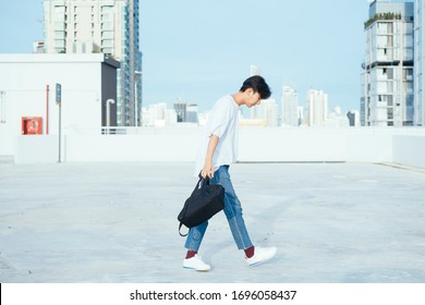 Teenage guy in jeans and white t-shirt walking on the rooftoop of high building in the city.