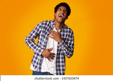 Teenage Guy Laughing Out Loud, Feeling Pain in Belly Muscles from Chuckle, Yellow Background