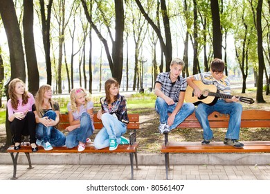 Teenage guy playing guitar, his friends listening