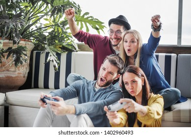 teenage guys and girls playing  exciting video games together with cheerful  friends with joysticks in hand.
