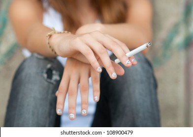 Teenage hands holding cigarette.