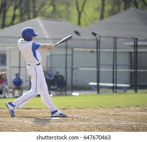 teenage high school baseball batter swinging