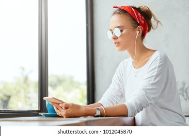 Teenage hipster girl relaxes at coffee shop with cup of espresso, listens music in playlist with earphones, sits against big window indoor, wears trendy sunglasses. Youth and technology concept