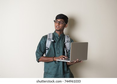 teenage indian male in traditional dress with laptop