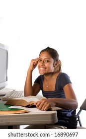 A teenage Latin/Hispanic girl working and studying.  In front of a computer with an open book. Happy, open eyes, white background.