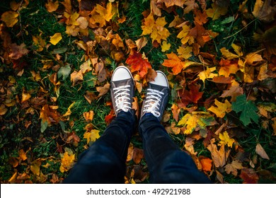 Teenage legs in sneakers and jeans standing on ground with autumn leaves, top view, unusual perspective