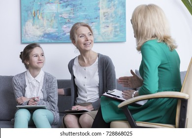 Teenage mental health and counseling concept, mother and daughter talking with female psychologist during session at office