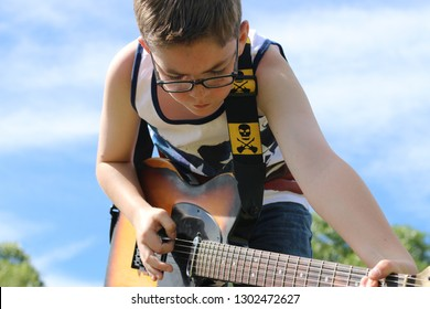 A teenage musician plays a guitar on stage at an outdoor concert in the summertime. A close lookup provides detail of the boy and guitar against the bright background sky.