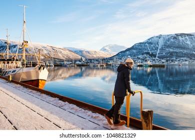 Teenage noy outdoors on winter day enjoying views of Tromso Norway