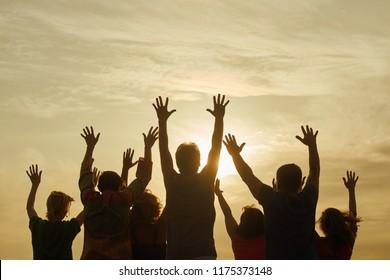 Teenage people having fun outdoor. Raising hands up while morning sunrise.