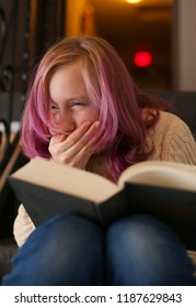 Teenage purple hair girl is reading a book. Different emotions.