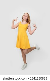 Teenage redhead girl happy dancing in yellow dress - full height portrait on gray background