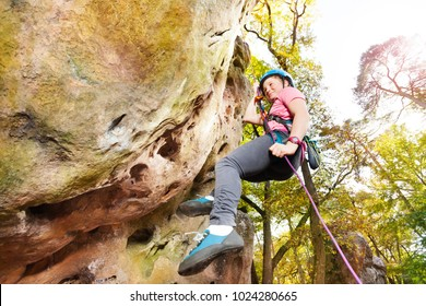 Teenage rock climber exercising at sunny day