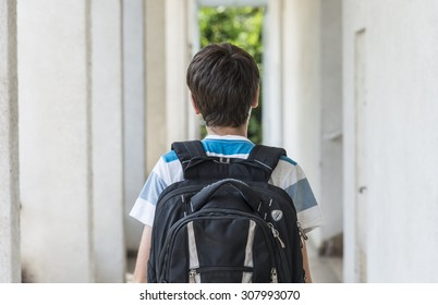 Teenage school boy with a backpack on his back walking to school. back view
