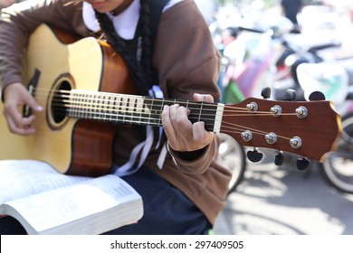 Teenage school girl playing an acoustic guitar with guitar song book
