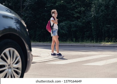 Teenage schoolgirl on pedestrian crossing in front of a car talking over the phone