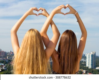 Teenage sisters holding hands together.Two female friends holding hands up in summer.Two young woman making heart shape with hands.Two young girl friends standing together,having fun.Amazing city view