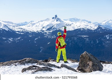 Teenage skier wearing read and green outfit with his hand up in the air on the top of Whistler with icon Rocky Mountains in the background.