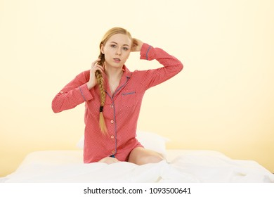 Teenage sleepwear fashion concept. Young woman lying on bed wearing cute pink pajamas