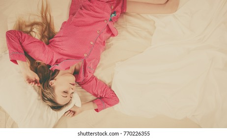 Teenage sleepwear fashion concept. Young woman lying on bed wearing cute pink pajamas. Top view