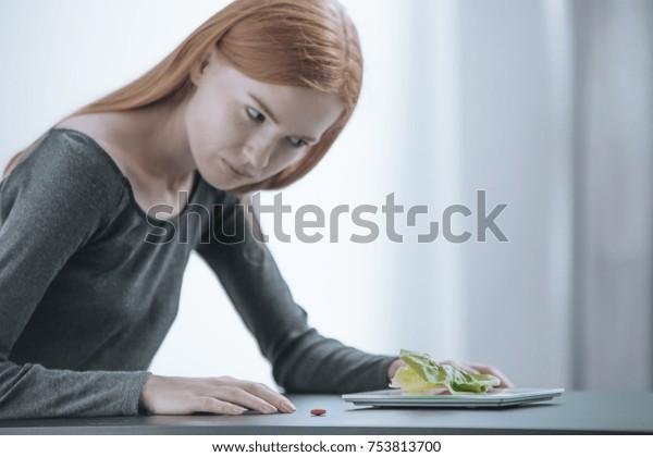 Teenage slim girl feeling sick while looking at breakfast. Eating disorders concept