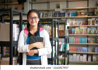 Teenage smart girl in glasses holding tablet and smiling at camera inside of school library