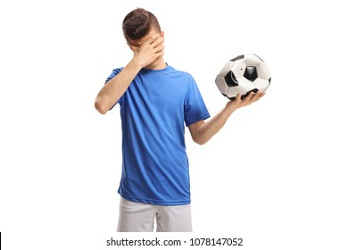 Teenage soccer player with a deflated football holding his head in disbelief isolated on white background