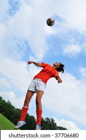 a teenage soccer player jumping up in the air with the ball