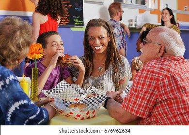 Teenage son eats a club sandwich while seated with his mother and grandparents