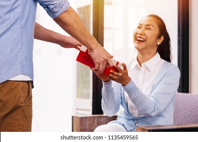 Teenage son giving a surprise gift and giving to middle aged mother on her special day such as mother's day or birthday. Celebration and holiday concept