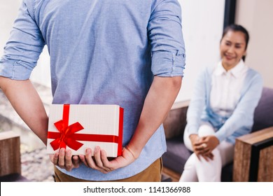 Teenage son hiding a surprise gift and giving to senior mother on her special day such as mother's day or birthday. Celebration and holiday concept