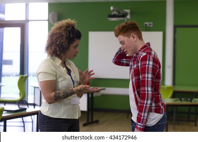 Teenage student being told off by his teacher at school.