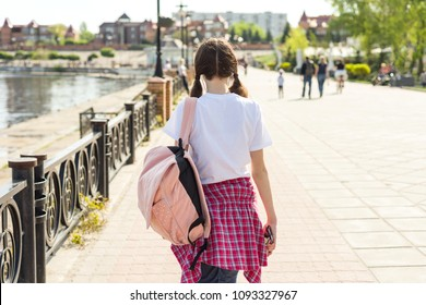 Teenage student girl walking down the street with backpack. Back to school, back view.