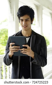 The teenage student man standing and holding tablet in hand.