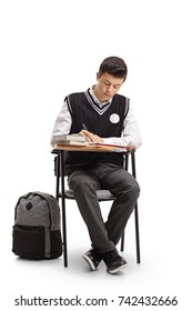 Teenage student sitting in a school chair and taking notes isolated on white background