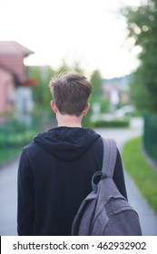 Teenage student standing with his back to the camera and a backpack on his shoulders.