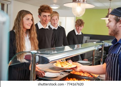 Teenage Students Being Served Meal In School Canteen
