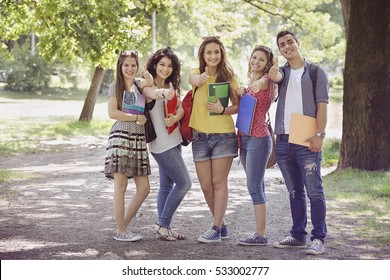 Teenage Students in the park with Thumbs up