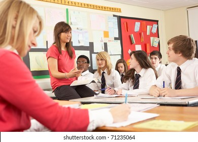 Teenage Students Studying In Classroom With Teacher And Assistant