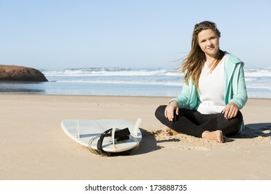 Teenage surfer girl sitting in the beach with her surfboard