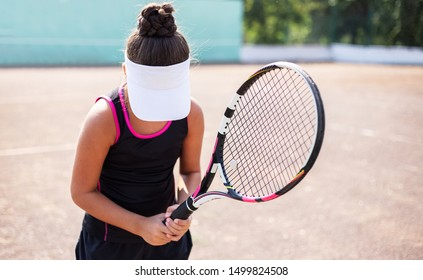 Teenage tennis girl with racket in hand waiting the serve.