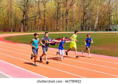 Teenage track sprinters running with British flag