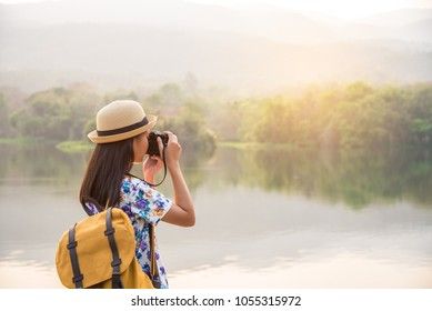 Teenage travelers with adventurous style, backpack, map hat, camera, by nature.