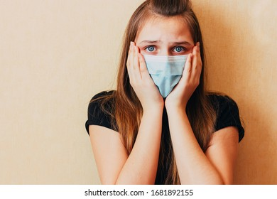 A teenage in viral protective medical mask looks with fear to camera with hands on cheeks. Girl afraid consequences of coronavirus epidemic. Shocking mortality and spread of virus around the world