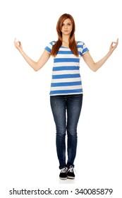 Teenage woman makes meditating gesture.