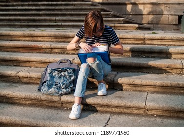 A teenage woman studying with a binder on the stairs of a university in a university campus
