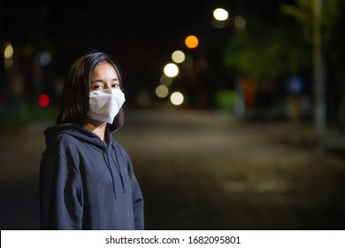 Teenage woman wearing a face mask during the COVID-19 contingency stop in the middle of the street when there is no traffic of people or cars, heeding the call to stay home.