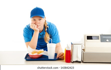 Teenage worker in a fast food restaurant bored and leaning on the counter.  White background.