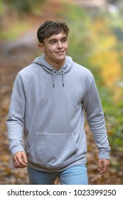 Teenage young adult walking along a woodland path on an autumn day