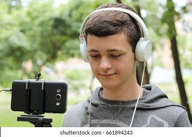 Teenage young boy in earphones looking at camera in mobile phone on the tripod and recording a fun video in the park, education and technology, outdoor summer portrait